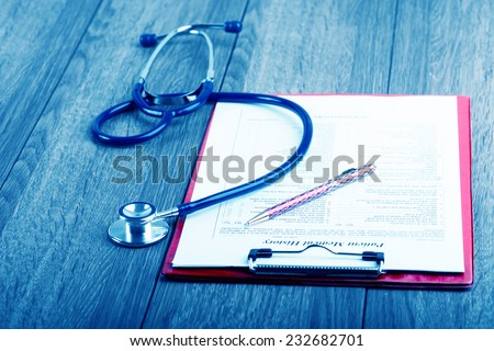 medical history with stethoscope and pen on wooden desk - stock photo