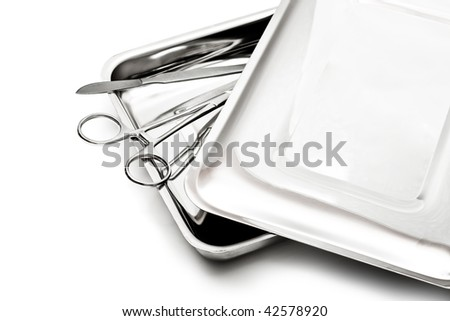 Medical instruments scalpel and clamp in a steel tray with a cover on a white background