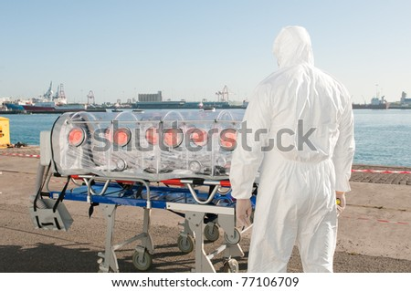 medical man with ambulance bed isolated for ebola, virus or nuclear alarm - stock photo