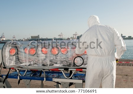medical man with ambulance bed isolated for virus or nuclear alarm - stock photo