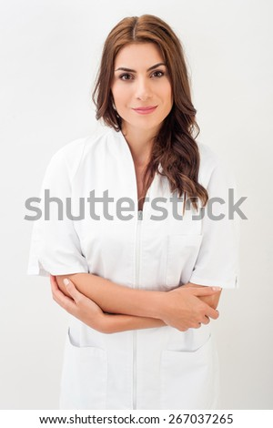 Medical nurse woman wearing white surgery suit, standing on white background. - stock photo