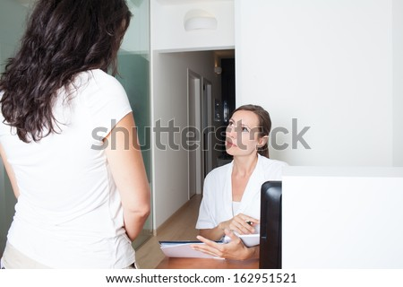Medical office assistant sets appointment with patient - stock photo