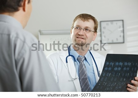 Medical office - middle-aged male doctor explaining computer tomograph scan to patient. - stock photo