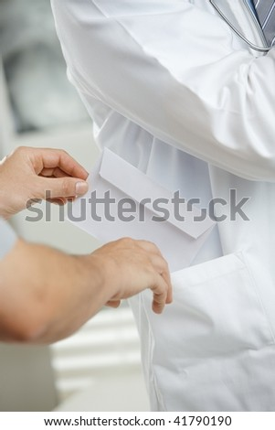 Medical office - patient bribing doctor, putting money in envelope to pocket. - stock photo