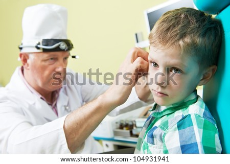 Medical otitus examination of a little child at a ear nose throat doctor - stock photo
