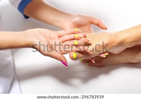 Medical pedicure. Beautician massaging woman's foot, acupressure treatment - stock photo