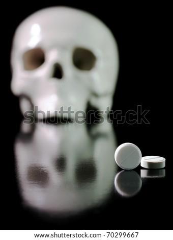 Medical pills and skull against black background. - stock photo