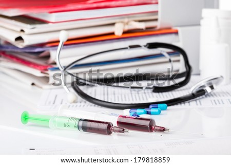 medical pills and syringes, stethoscope on the medical claim form