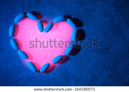 Medical pills on textured background with blue lighting. Pills are arranged in the form of a heart and are lit with red light. - stock photo