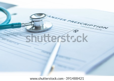 Medical prescription blank paper form for patients record with doctor's stethoscope & pen for writing on working table/ desk: Physician note on empty RX paperwork in hospital/ clinic office interior - stock photo