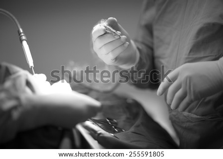 Medical procedures, hands of a surgeon - stock photo