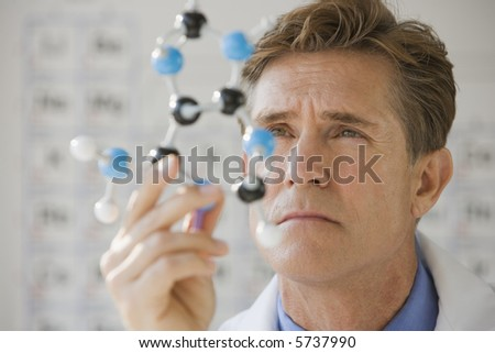 Medical professional examining a chemical molecule - stock photo