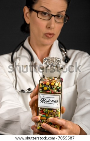 Medical professional in white coat showing vintage medicine pill glass - stock photo