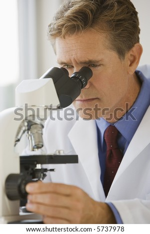 Medical professional looking through a microscope - stock photo