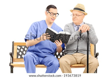Medical professional reading to an elderly seated on bench isolated on white background - stock photo