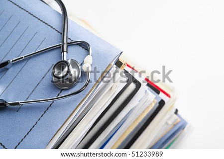Medical record concept with stethoscope over pile of document. Selective focus on the front side of the stethoscope - stock photo