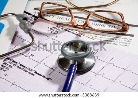 Medical records that a doctor would review, contains eye glasses and stethoscope, and EKG
