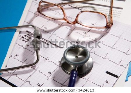 Medical records that a doctor would review, contains eye glasses and stethoscope, and EKG - stock photo
