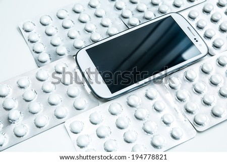Medical smartphone. A modern cellphone with pills. - stock photo