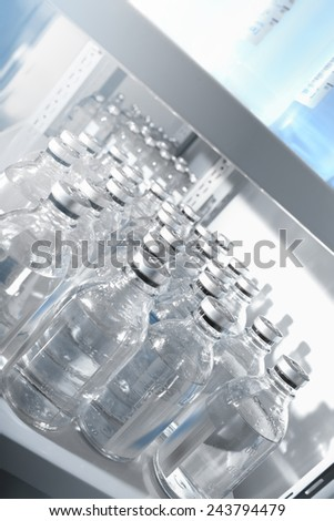 Medical solutions in bottles standing in warehouse - stock photo