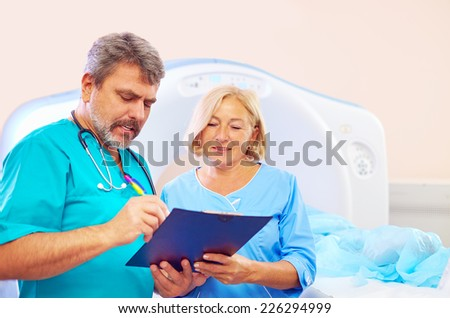 medical staff filling application form for CT scanner procedure - stock photo