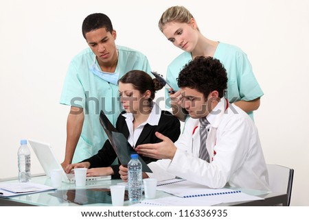 Medical staff gathered by desk - stock photo