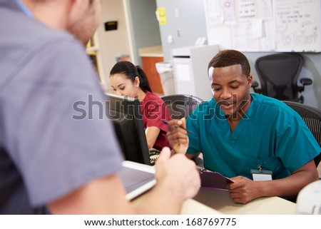 Medical Staff Meeting At Nurses Station - stock photo