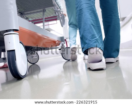 Medical staff moving patient through hospital corridor  - stock photo