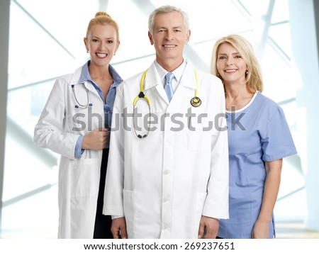 Medical staff portrait. Female doctor and male doctor standing with nursing assistant at hospital while smiling and looking at camera.  - stock photo