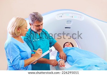 medical staff preparing patient to CT scanner procedure - stock photo