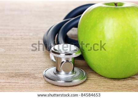 Medical stethoscope and apple on wooden background - stock photo