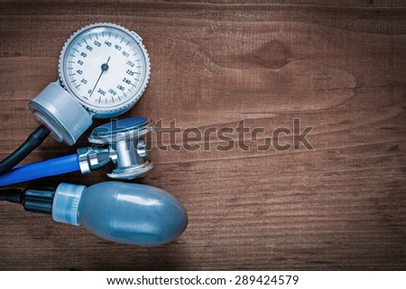 Medical stethoscope and blood pressure monitor on vintage wooden pine board medicine concept  - stock photo