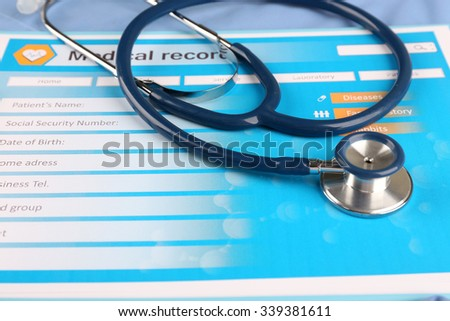 Medical stethoscope and clipboard on blue background - stock photo