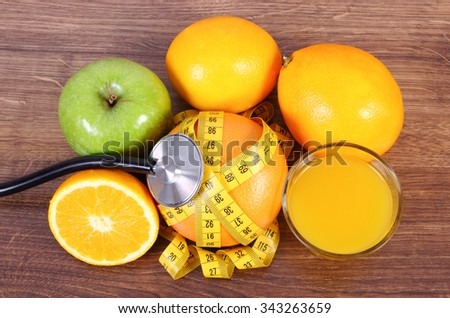 Medical stethoscope and tape measure with fresh ripe fruits and glass of juice on wooden surface plank, grapefruit orange apple, healthy lifestyles and nutrition - stock photo