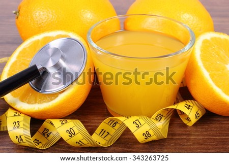 Medical stethoscope, fresh ripe orange, glass of juice and tape measure on wooden surface plank, healthy lifestyles nutrition and strengthening immunity - stock photo