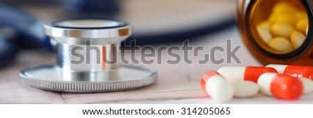 Medical stethoscope head lying on cardiogram chart with pile of pills closeup. Cardiology care, health, protection, prevention and help. Healthy life or insurance concept. Letterbox view - stock photo