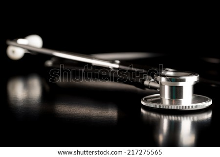 Medical stethoscope lying on a reflective black surface with a close up view of the metallic disc for listening to the internal sounds of the body such as heartbeat and lungs, with copyspace. - stock photo