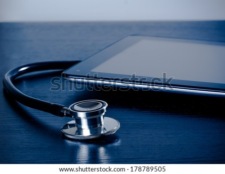 medical stethoscope near modern digital tablet pc in laboratory on wood table. Concept of medical or research theme - stock photo