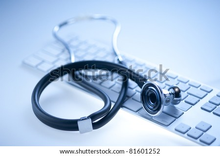 Medical stethoscope on a  computer keyboard in blue, closeup - stock photo
