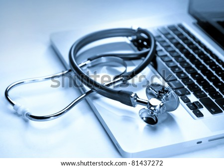 Medical stethoscope on a laptop computer in blues, closeup - stock photo