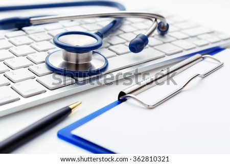 Medical stethoscope on computer keyboard with clipboard