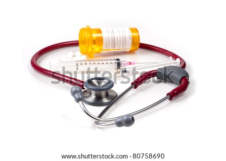 Medical stethoscope, pill bottles and syringes against a white background.