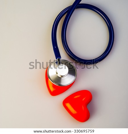 Medical stethoscope rests on a pair of red hearts - stock photo