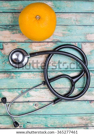Medical stethoscope with an orange fruit. Healthy lifestyle concept image