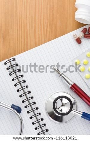 medical stethoscope with pills and notebook on wood