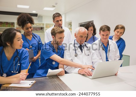 Medical students and professor using laptop at the university - stock photo