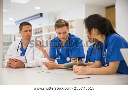Medical students sitting and talking at the university - stock photo
