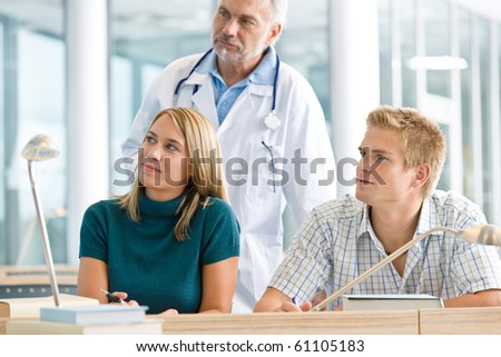 Medical students with professor in classroom studying
