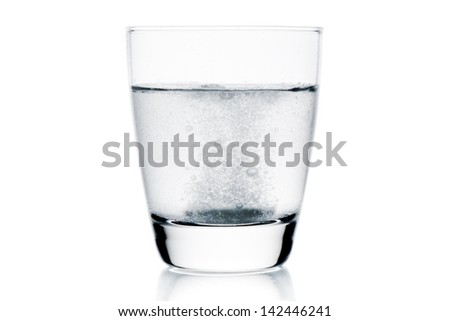 medical tablet dropped into the water with bubbles on white background