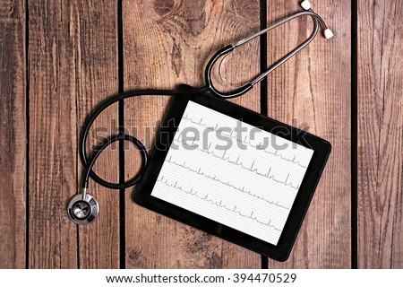 Medical tablet with stethoscope on wooden background - stock photo